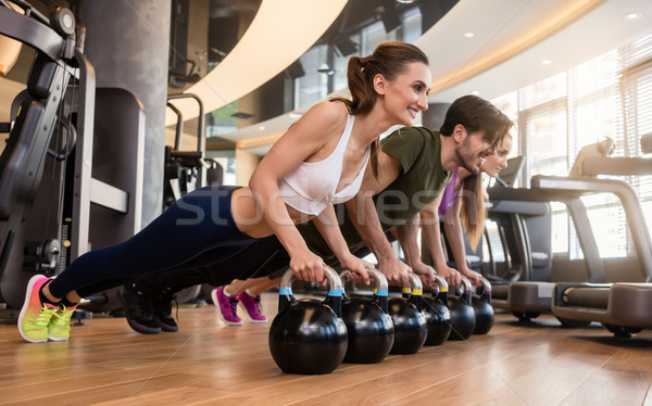 Three young people doing the kettlebell plank challenge during g Stock photo © Kzenon