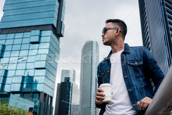 Stock photo: Young man wearing blue denim jacket while daydreaming outdoors i