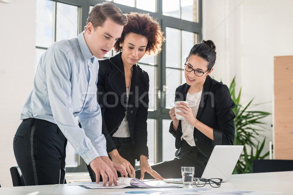 Employees checking together documents and business reports Stock photo © Kzenon