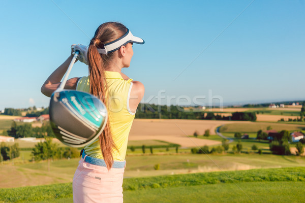 Young woman holding a driver club during golf swing at the begin Stock photo © Kzenon