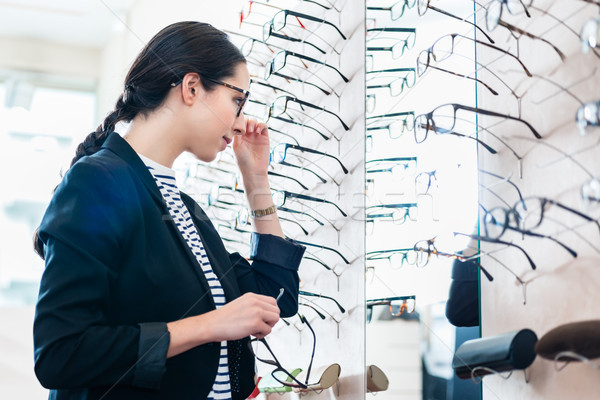 Woman taking glasses off shelf in optician shop Stock photo © Kzenon