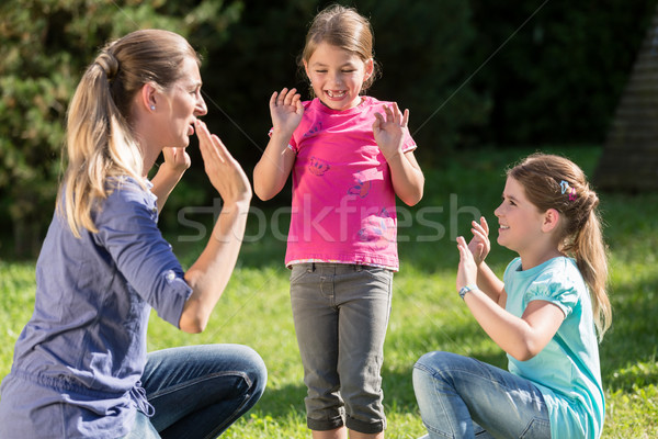 Mother with children daughters doing dance exercise outdoors Stock photo © Kzenon