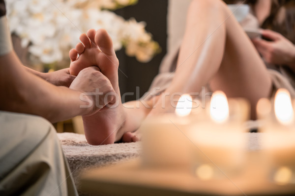 Woman having reflexology foot massage in wellness spa Stock photo © Kzenon