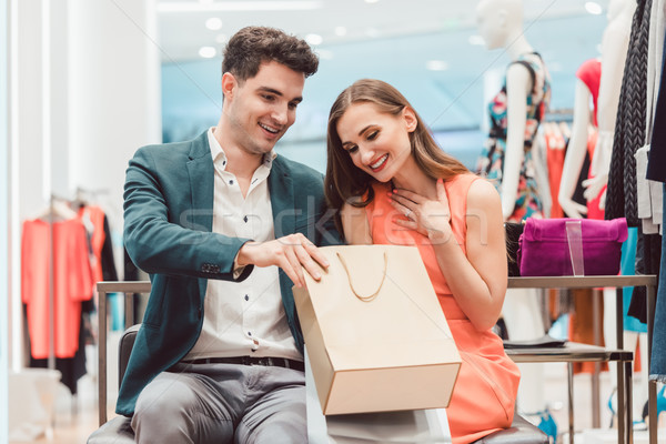 Woman showing her man what she bought in fashion store Stock photo © Kzenon