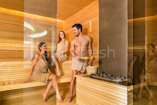 Young and beautiful people smiling while socializing in a wooden dry sauna Stock photo © Kzenon