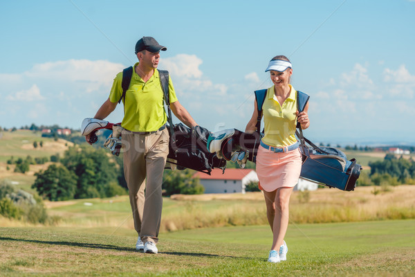 Stock photo: Happy couple wearing golf outfits and carrying stand bags