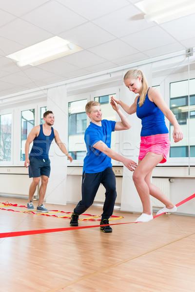 Physio practicing slacklining with athletes in gym Stock photo © Kzenon