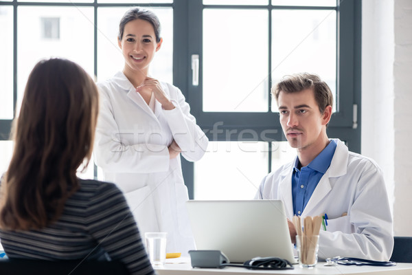 Young nurse listening to an experienced physician while consulting a patient Stock photo © Kzenon