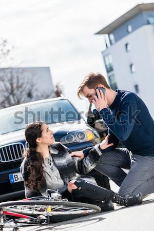 Young man calling the emergency services after hitting a bicyclist Stock photo © Kzenon