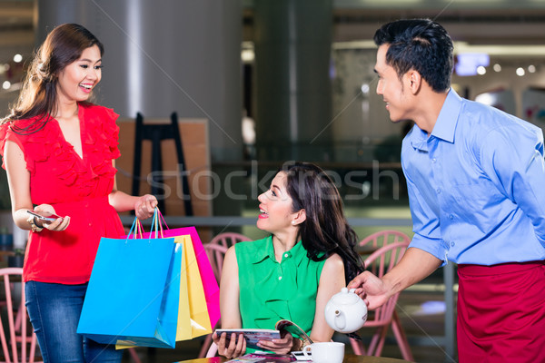 Fashionable young woman looking happy for meeting a friend in a coffee shop Stock photo © Kzenon