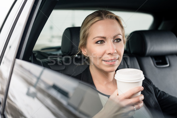 Businesswoman holding coffee cup sitting in the car Stock photo © Kzenon