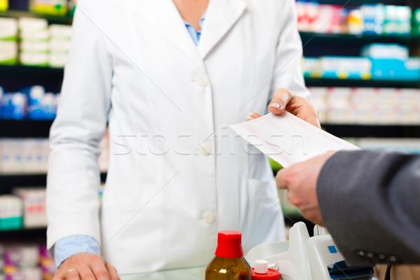Female pharmacist with customer in pharmacy Stock photo © Kzenon
