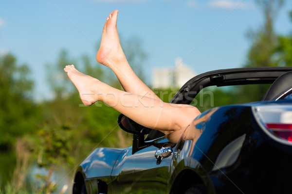 Young woman or her legs in a cabriolet Stock photo © Kzenon