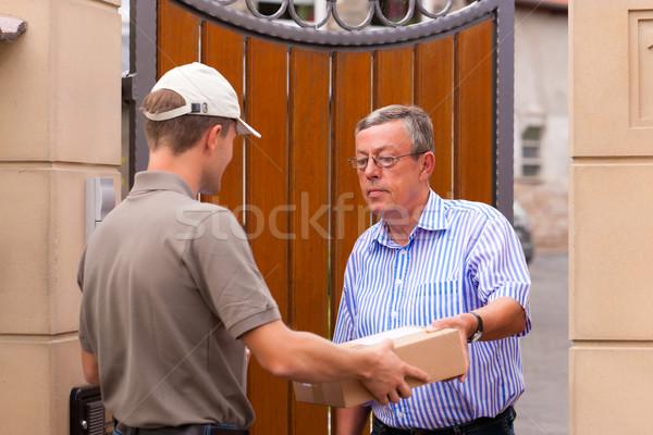 Почтовая служба доставки пакет почтальон клиентов дома Сток-фото © Kzenon
