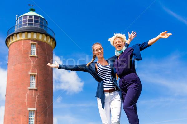 Friends standing at lighthouse on ocean Stock photo © Kzenon