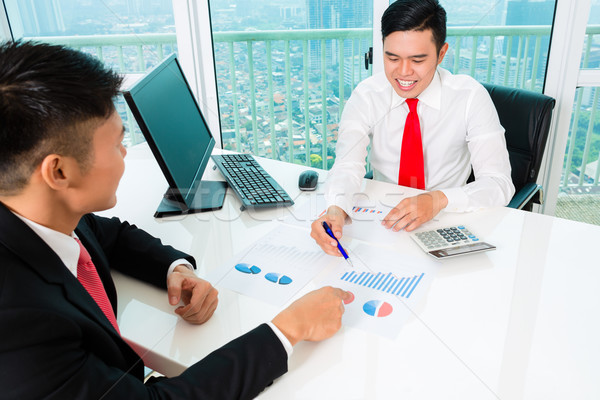 Stock photo: Asian banker counseling financial investment