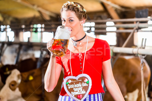 Countrywoman drinking beer in cowhouse Stock photo © Kzenon