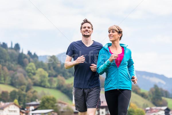 Couple doing sport running in the mountains Stock photo © Kzenon