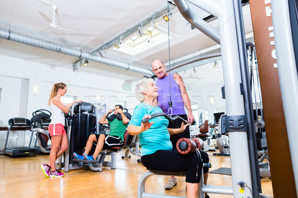 Senior woman doing back training with trainer in gym Stock photo © Kzenon