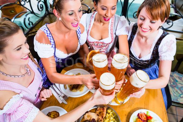 Girls toasting with wheat beer in Bavarian pub Stock photo © Kzenon