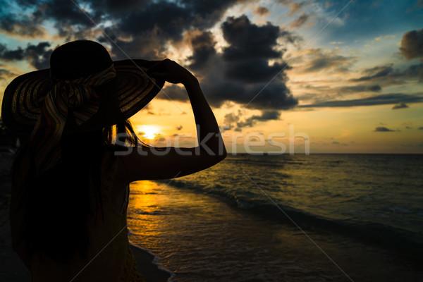Tourist woman watching sunset at ocean beach Stock photo © Kzenon