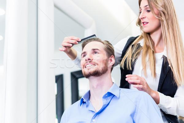 Haircutter cutting hair of customer Stock photo © Kzenon
