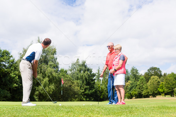 Golf pro practicing the sport with senior woman and man  Stock photo © Kzenon