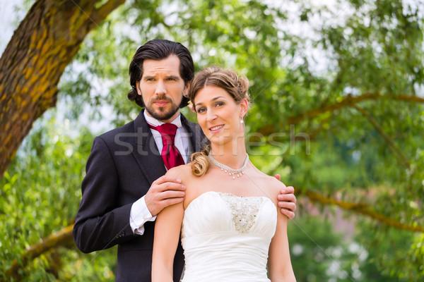 Bridal pair in park, groom holding bride Stock photo © Kzenon