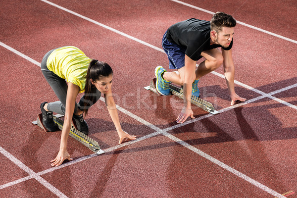 Male and female athlete in starting position at starting block o Stock photo © Kzenon