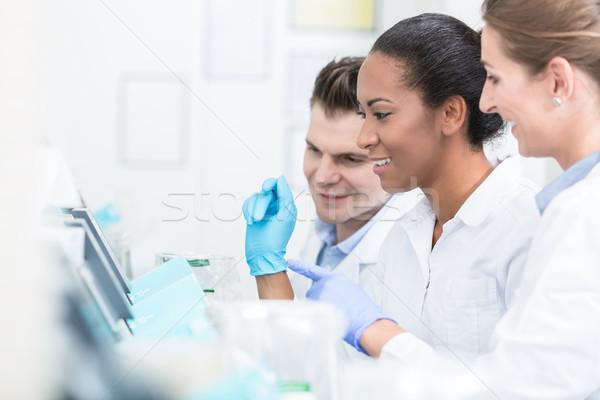 Grupo trabalhar dispositivos laboratório mulher homem Foto stock © Kzenon