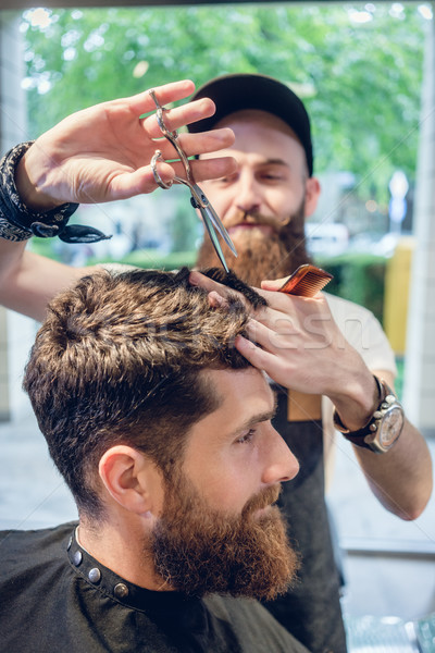 Dedicated hairstylist using scissors and comb while giving a coo Stock photo © Kzenon