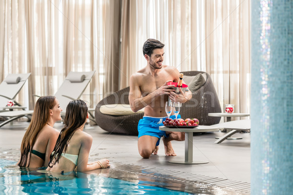 Young man serving with champagne two women at the swimming pool  Stock photo © Kzenon