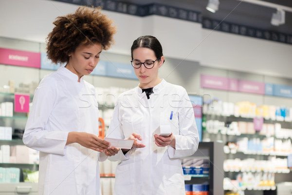 Two pharmacists analyzing the package of a new pharmaceutical drug Stock photo © Kzenon
