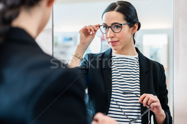 Woman looking with glasses in mirror at optician Stock photo © Kzenon
