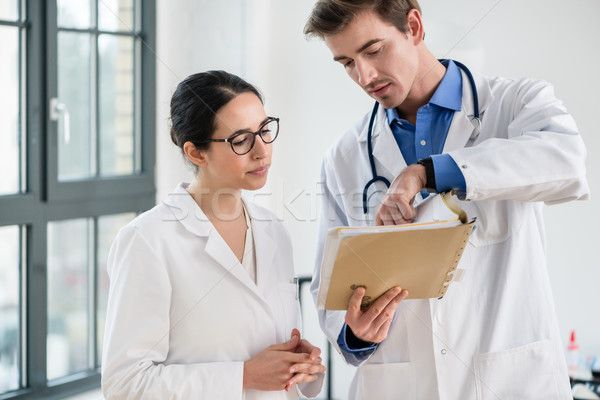 Two doctors checking together the medical record of a patient Stock photo © Kzenon