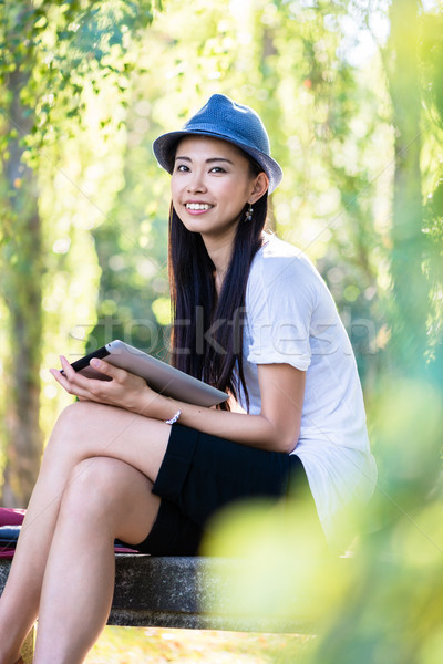 Asian woman using a tablet PC outdoors Stock photo © Kzenon