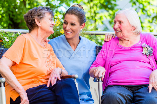 Geriatric nurse having chat with senior women Stock photo © Kzenon