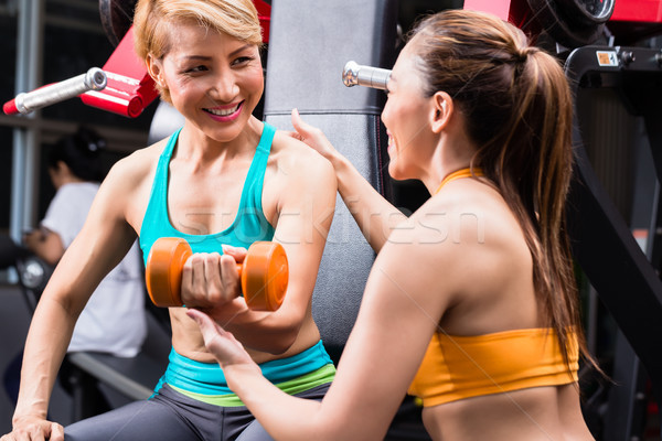 Women assisting girl during dumbbell gym exercises Stock photo © Kzenon