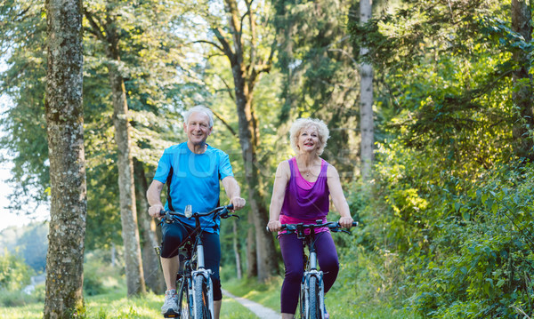 Happy and active senior couple riding bicycles outdoors in the park Stock photo © Kzenon
