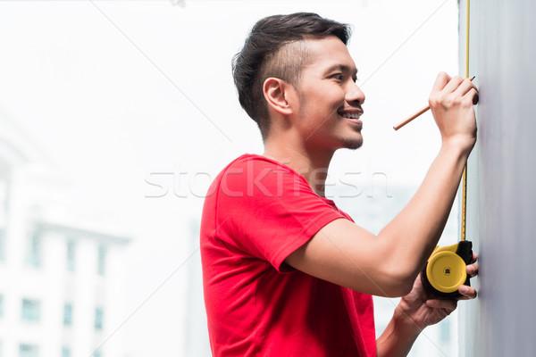 Jóvenes indonesio hombre cinta métrica rascacielos edificio Foto stock © Kzenon