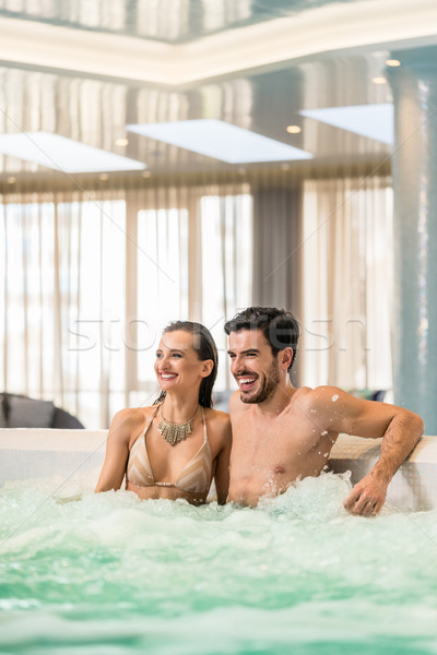 Stock photo: Young and happy couple in love relaxing in jacuzzi of spa or luxury hotel