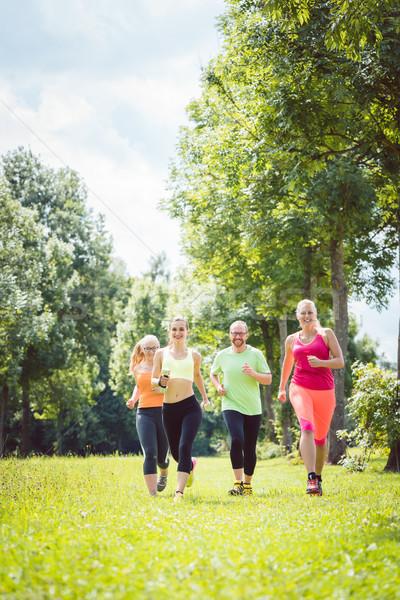 Family with personal Fitness Trainer jogging Stock photo © Kzenon