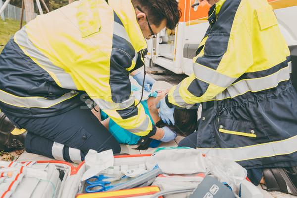 Paramedics performing first aid at ambulance Stock photo © Kzenon