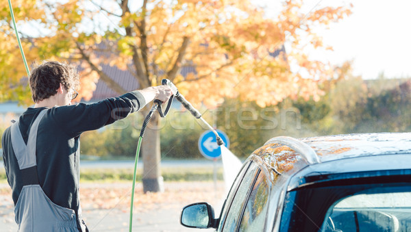 Worker cleaning car with high pressure water nozzle Stock photo © Kzenon