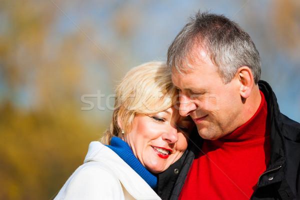Retired senior couple embracing in park Stock photo © Kzenon