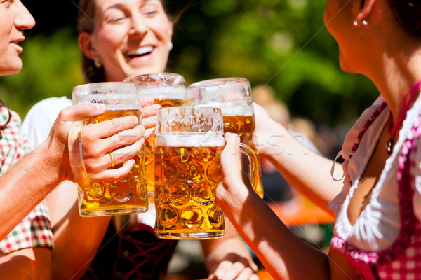 Two happy couple sitting in Beer garden Stock photo © Kzenon