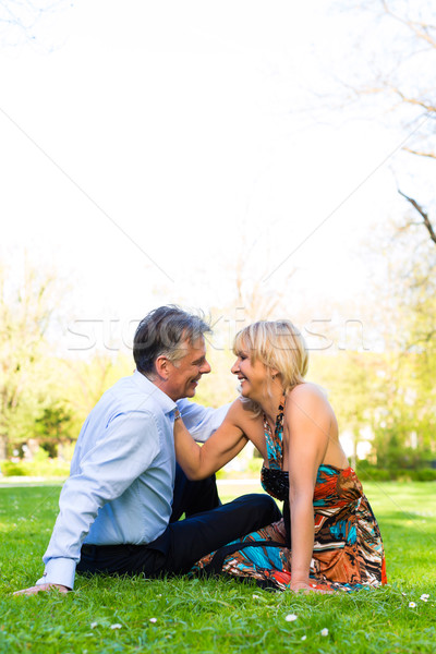 Senior couple during spring on a meadow in the city Stock photo © Kzenon