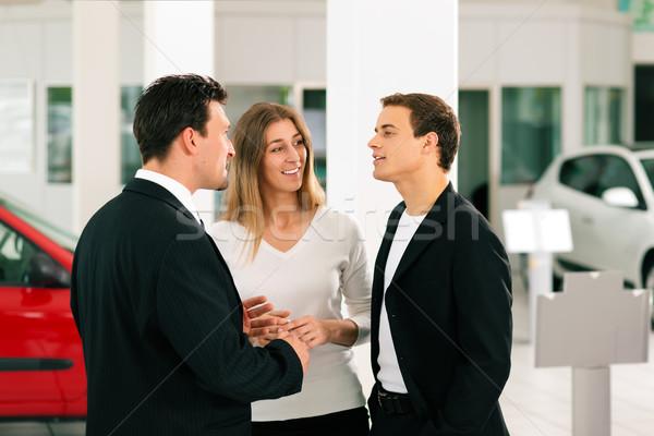 Couple with salesman at car dealer  Stock photo © Kzenon