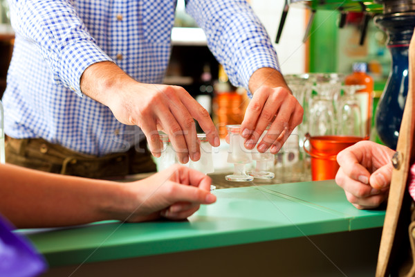 Barkeeper pouring hard liquor in glasses Stock photo © Kzenon