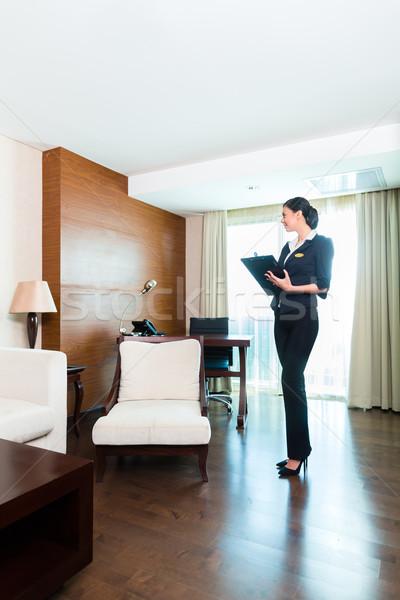 Asian executive housekeeper controlling hotel room Stock photo © Kzenon